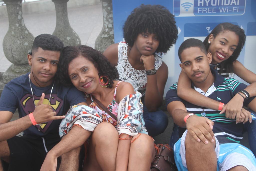 Foto com 5 pessoas sentadas e olhando para a câmera. Há uma mulher adulta, e 4 adolescentes - 2 meninos e 2 meninas.