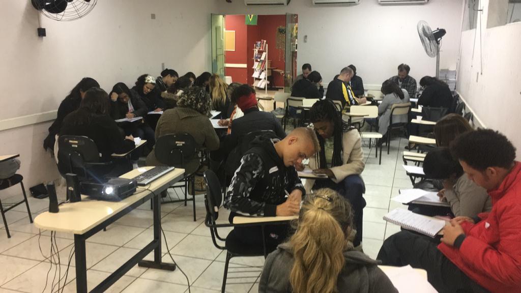 Foto de pessoas sentadas em carteiras numa sala de aula realizando atividade escrita.