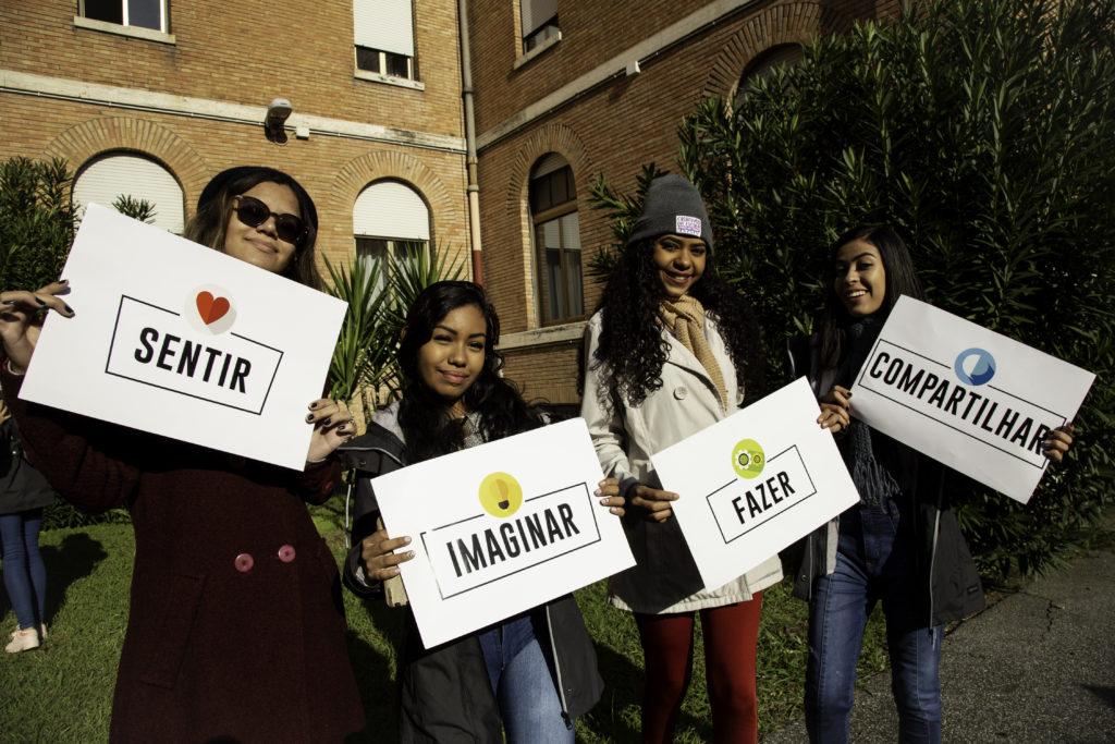 Foto de 4 adolescentes, cada uma segura uma placa com verbos e ícones. Da esquerda para direita: sentir e um coração, imaginar e uma lâmpada, fazer e uma engrenagem e compartilhar e um balão de fala