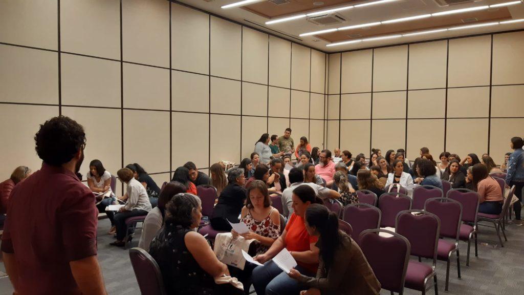Foto de um grupo de pessoas sentado em uma sala. Há uma pessoa em pé ministrando uma palestra.