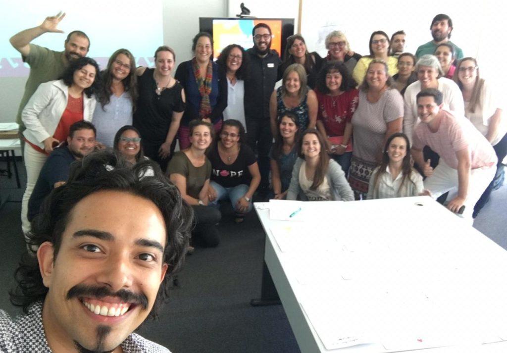 Foto com cerca de 30 pessoas em uma sala de reunião. Todas estão sorrindo. E no, primeiro plano, há um homem que está tirando a selfie.